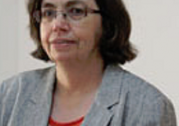 Official Statistics: Nancy McBeth wearing glasses and grey blazer looking to the left